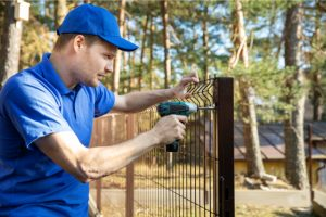 Beaverton Fence Installation by worker with a power tool