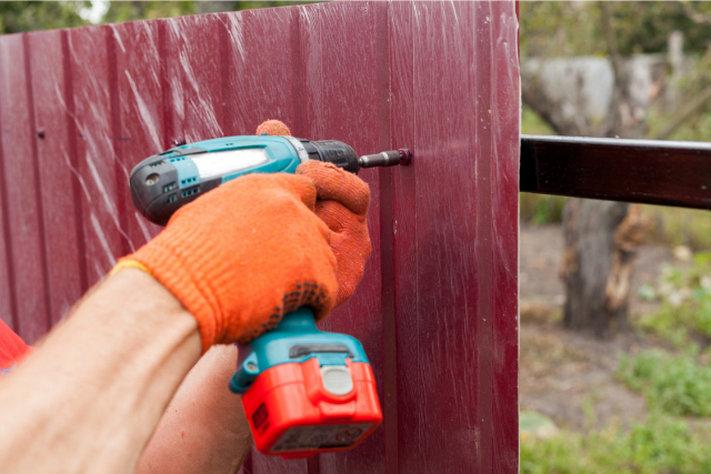 Metal fence installation by worker in gloves with a drill